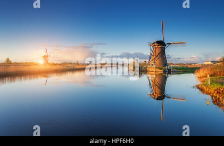Windmills at sunrise. Rustic landscape with amazing dutch windmills near the water canals with blue sky and clouds - Stock Photo
