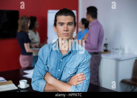 Portrait of business executive standing with arms crossed at meeting in office - Stock Photo