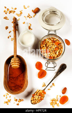 Homemade granola (with dried fruit and nuts) and healthy breakfast ingredients - honey, milk and fruits on white - Stock Photo