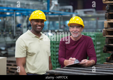 Portrait of two factory workers standing with clipboard in drinks production plant - Stock Photo