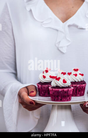 A woman with a white dress holding a cake stand full of red velvet cupcakes photographed from front view. - Stock Photo