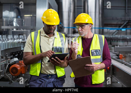 Two factory workers with clipboard and digital tablet working at drinks production plant - Stock Photo