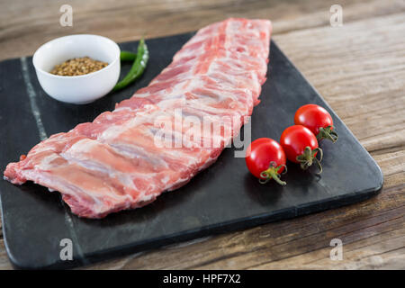 Raw beef ribs, chillies, cherry tomatoes and coriander seeds on slate board - Stock Photo