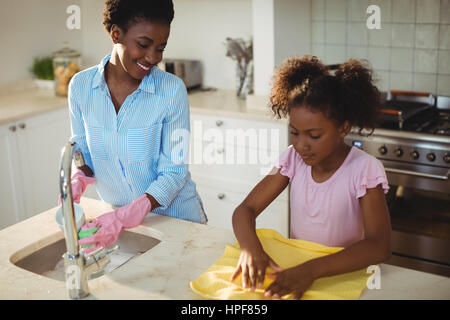 Mother assisting her daughter in cleaning utensils at home - Stock Photo