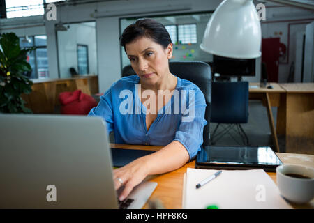 Female graphic designer using laptop in creative office - Stock Photo