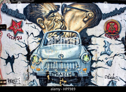 East Side Gallery. Brezner and Honecker kissing itself on trabi crossing the wall. Berlin. Germany - Stock Photo