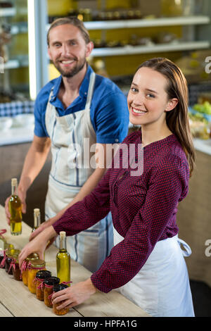 Portrait of shop assistants arranging jam and pickle jars at grocery shop - Stock Photo