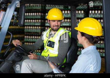 Smiling factory workers interacting with each other in factory - Stock Photo