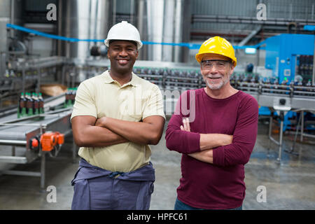 Portrait of two factory workers standing with their arms crossed in drinks production plant - Stock Photo