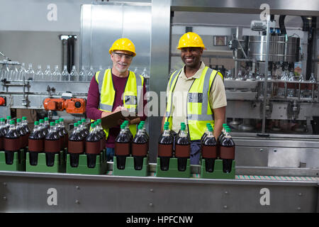 Portrait of two factory workers monitoring cold drink bottles at drinks production plant - Stock Photo