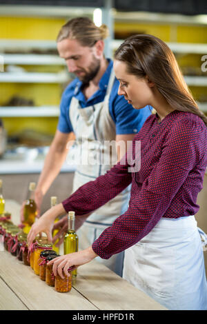 Shop assistants arranging jam and pickle jars at grocery shop - Stock Photo