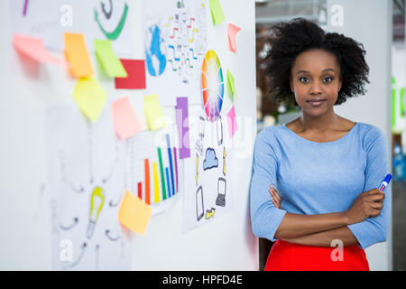 Portrait of female graphic designer standing with hands crossed in creative office - Stock Photo