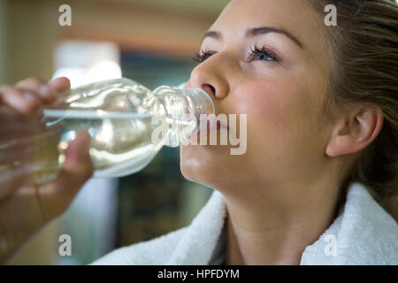 Beautiful woman drinking water after workout in gym - Stock Photo