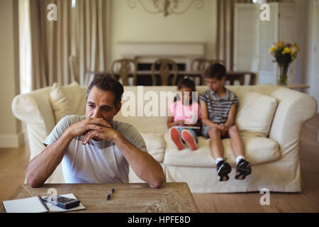 Thoughtful man sitting in living room at home - Stock Photo