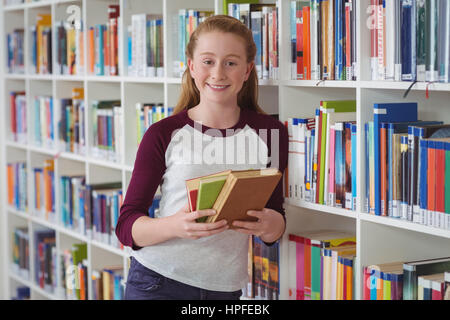Portrait of happy schoolgirl holding books in library at school - Stock Photo
