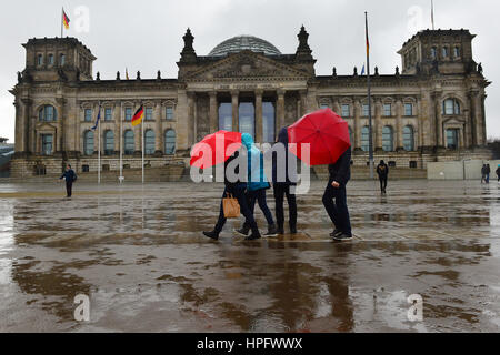 Berlin, Germany. 22nd Feb, 2017. Passers-by walking past the Reichstag through pouring rain in Berlin, Germany, - Stock Photo