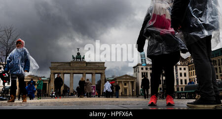 Berlin, Germany. 22nd Feb, 2017. Tourists with plastic rain protection in front of the Brandenburg Gate after a - Stock Photo
