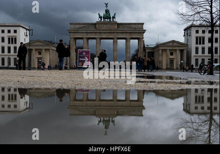 Berlin, Germany. 22nd Feb, 2017. The Brandenburg Gate can be seen reflected in a puddle in after a rain shower in - Stock Photo
