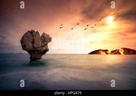 Fine art with lonely rock sculpture in the sea with silhouettes of flying birds and a burning island under sunset. - Stock Photo