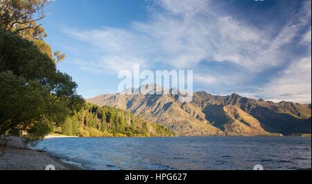Queenstown, Otago, New Zealand. Panoramic view across Lake Wakatipu to Cecil Peak, evening. - Stock Photo