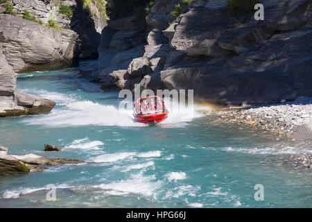 Queenstown, Otago, New Zealand. Shotover Jet boat emerging from narrow canyon on the Shotover River. - Stock Photo