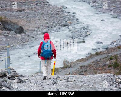 Fox Glacier, Westland Tai Poutini National Park, West Coast, New Zealand. Hiker descending slope on the Fox Glacier - Stock Photo
