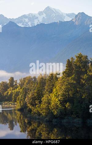 Fox Glacier, Westland Tai Poutini National Park, West Coast, New Zealand. View across tranquil Lake Matheson to - Stock Photo