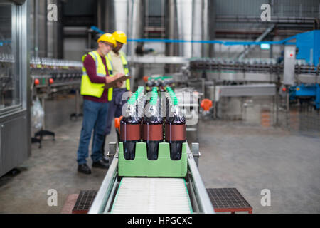 Two factory workers monitoring cold drink bottles on production line at drinks production plant - Stock Photo