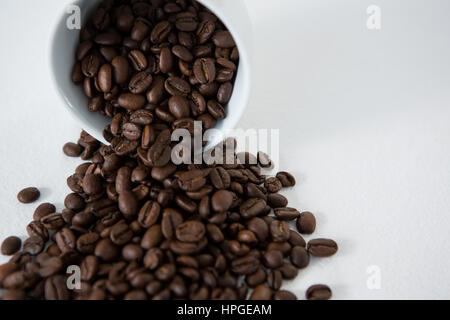 Roasted coffee beans spilling out of cup on wooden table - Stock Photo