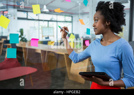 Female graphic designer writing on glass with marker - Stock Photo