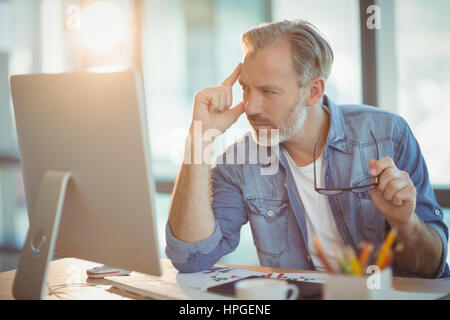 Male graphic designer working on computer in office - Stock Photo