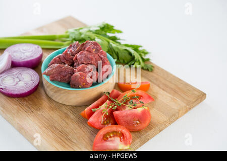 Minced beef and ingredients on wooden tray against white background - Stock Photo