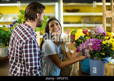 Happy couple selecting flowers in the florist shop - Stock Photo