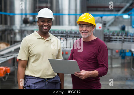 Portrait of two factory workers with laptop smiling in the drinks production plant - Stock Photo