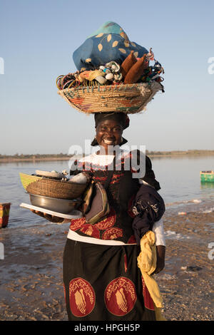 Fitou carrying her wares on the shores of Lac Rose or Lake Retba in Senegal - Stock Photo