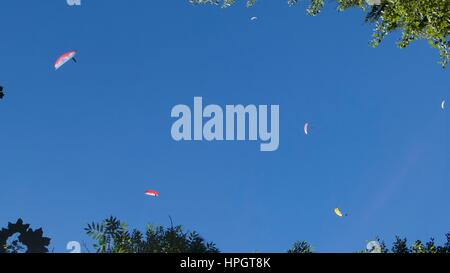Low angle view of a group of paragliders paragliding in blue sky, Chamonix, Mont Blanc, France - Stock Photo