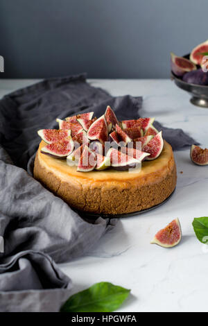 Whole cheesecake decorated with fresh figs on a marble table. Vertical view, copy space for text - Stock Photo