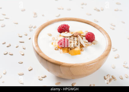 Yogurt bowl with fresh raspberries, apricots and muesli in a wooden bowl on white background. Meal for healthy breakfast, - Stock Photo