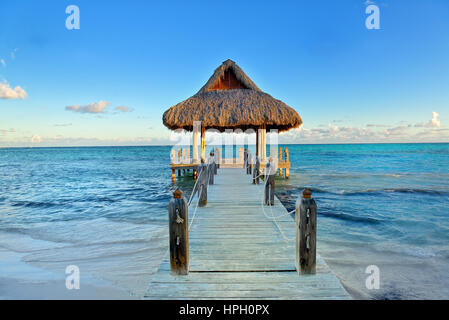 Tropical white sandy beach. Palm leaf roofed wooden pier with gazebo on the beach. Punta Cana, Dominican Republic - Stock Photo