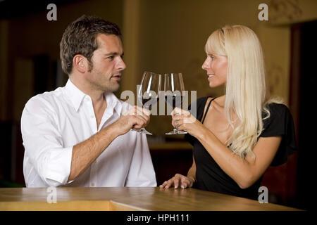 Model released , Mann und Frau sitzen mit Wein an der Bar - couple drinks wine at the bar - Stock Photo