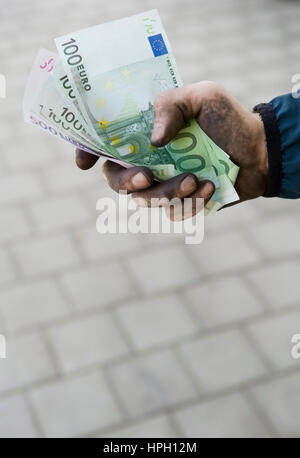 Model released , Symbolbild Schwarzgeld, Arbeiter mit schmutzigen Haenden haelt Geldscheine - symbolic for black - Stock Photo
