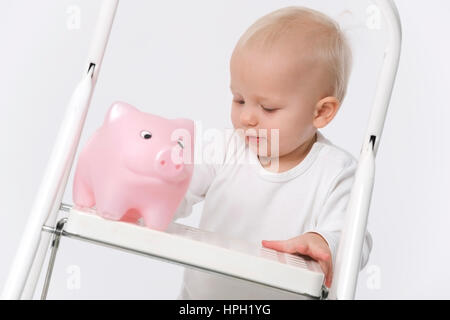Model released , Kleinkind mit Sparschwein auf der Leiter - little child with piggy bank on ladder - Stock Photo