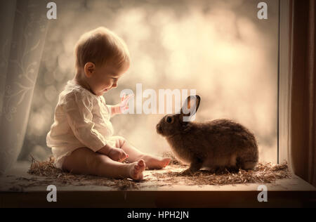 A baby playing with a brown rabbit - Stock Photo