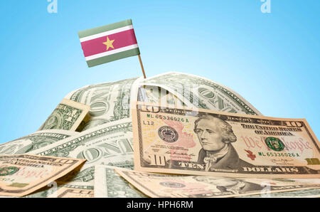 The national flag of Suriname sticking in a pile of american dollars.(series) - Stock Photo