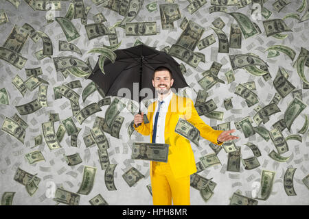 Young rich businessman standing in money rain - Stock Photo