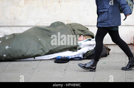 Homeless man sleeping rough on streets of Brighton as passer by walks past - Stock Photo