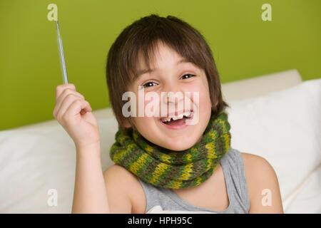 Froehlicher Junge mit Fieberthermometer in der Hand hat kein Fieber mehr - little boy is helath again, Model released - Stock Photo