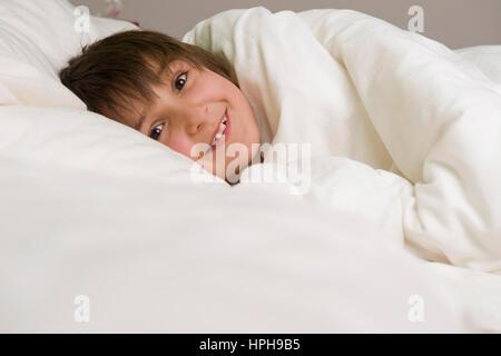Kleiner Junge liegt froehlich im Bett - boy lucky in bed, Model released - Stock Photo