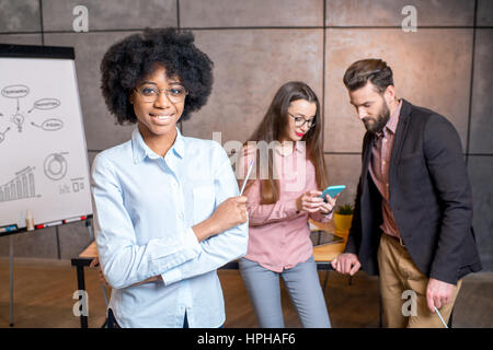 Woman's portrait with coworkers - Stock Photo