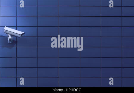Horizontal front view of a surveillance monitoring white camera viewed from a side with blue background wall of - Stock Photo